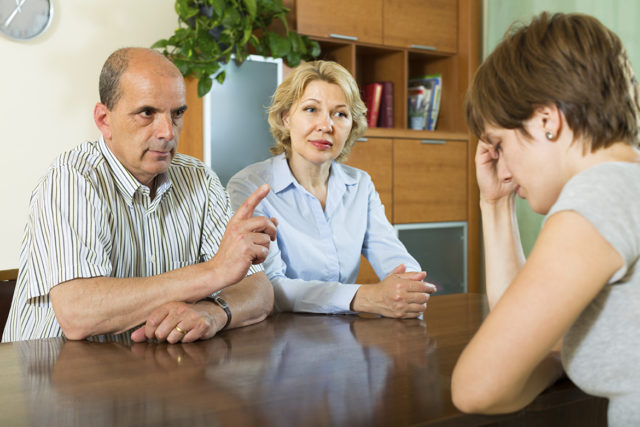 Mature parents berating adult daughter in home interior